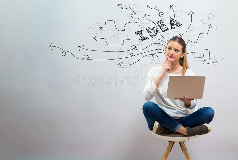Brainstorming idea arrows with young woman using her laptop. On a grey background royalty free stock photography