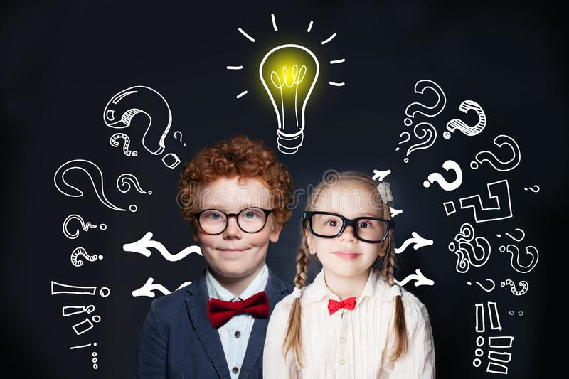 Brainstorming and idea concept. Smart successful children girl and boy student with lightbulb on blackboard background royalty free stock photos