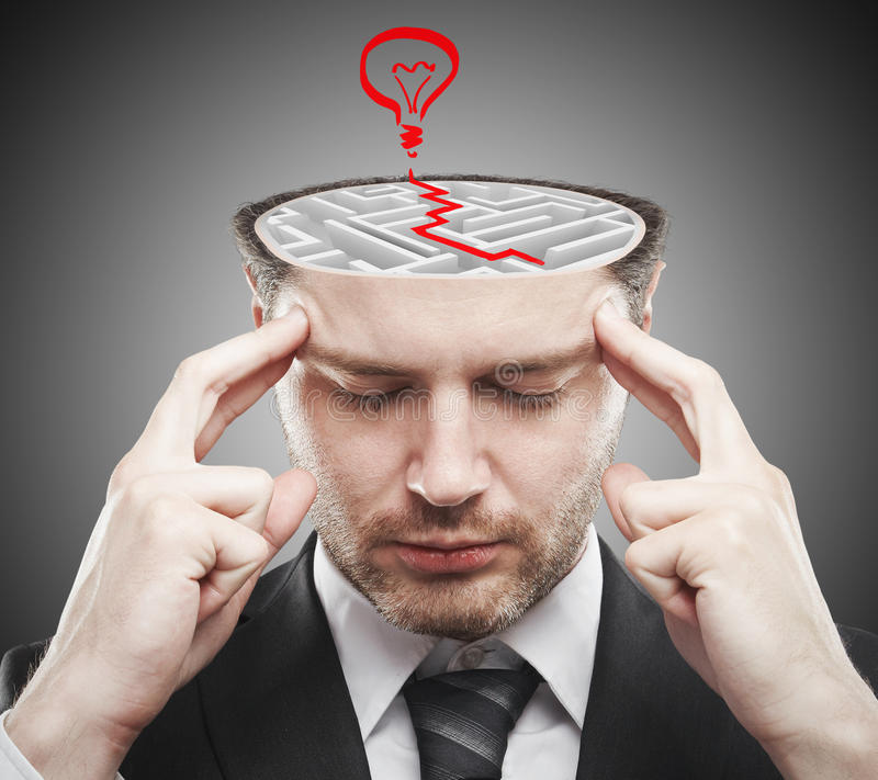 Brainstorming ideas concept. Thoughtful young businessman with abstract concrete maze and red lamp sketch inside head. Brainstorming ideas concept royalty free stock images