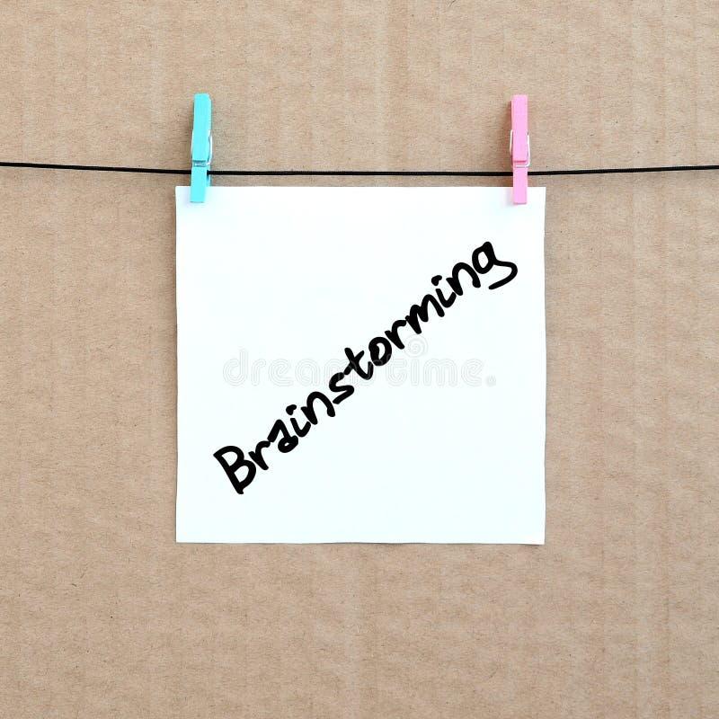 brainstorming La nota se escribe en una etiqueta engomada blanca que cuelgue ingenio fotos de archivo