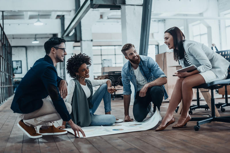 Brainstorming for a new project. Group of confident business people in smart casual wear communicating together and smiling while working in the modern office stock photography