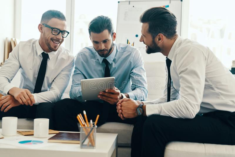 Brainstorming together. Group of young modern men in formalwear working using digital tablet while sitting in the office stock photos