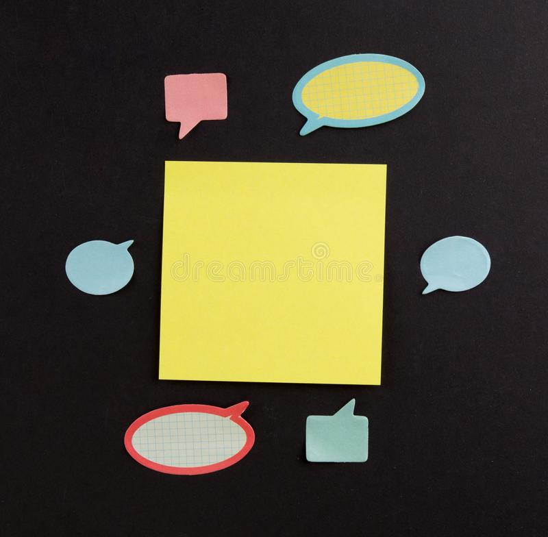 Brainstorming- und Ideenkonzept Große gelbe klebrige Anmerkung umgeben durch viele kleinen Dialoganmerkungen über Rückenbrett lizenzfreie stockfotos