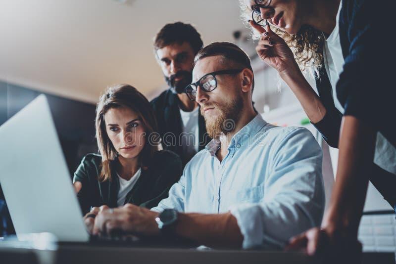 Brainstormingprozeß im Büro Junge Mitarbeiter arbeiten modernes Bürostudio zusammen Junge Geschäftsteamherstellung lizenzfreie stockfotos