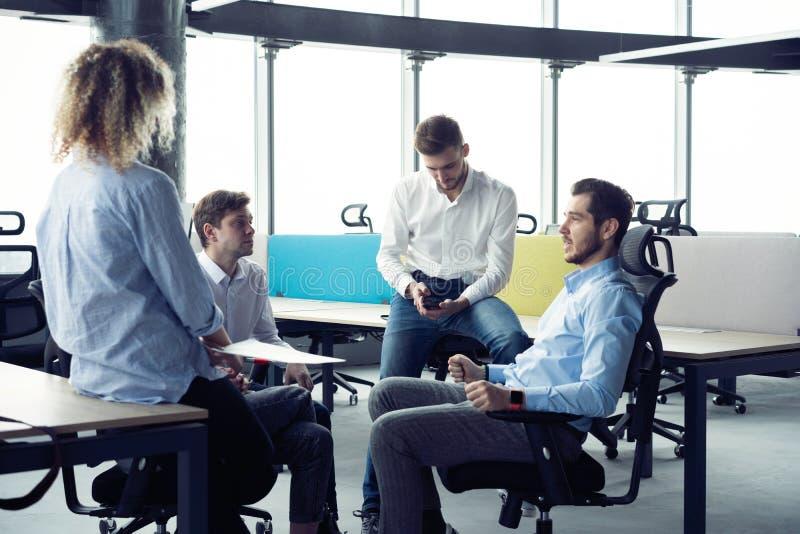 brainwaves Группа в составе молодые современные люди в умной случайной носке имея встречу в творческом офисе стоковое изображение
