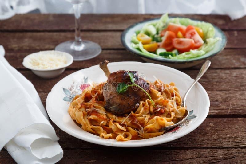 Braised нога кролика в томатном соусе с домодельными макаронными изделиями, темной деревенской предпосылкой стоковая фотография rf