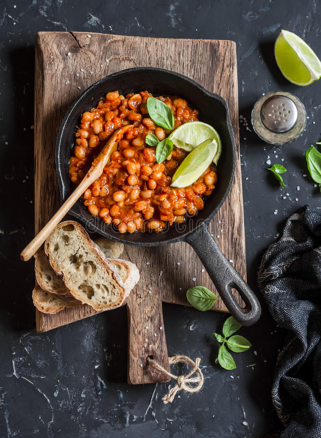 Braised beans in tomato sauce in a cast iron pan and homemade bread royalty free stock images