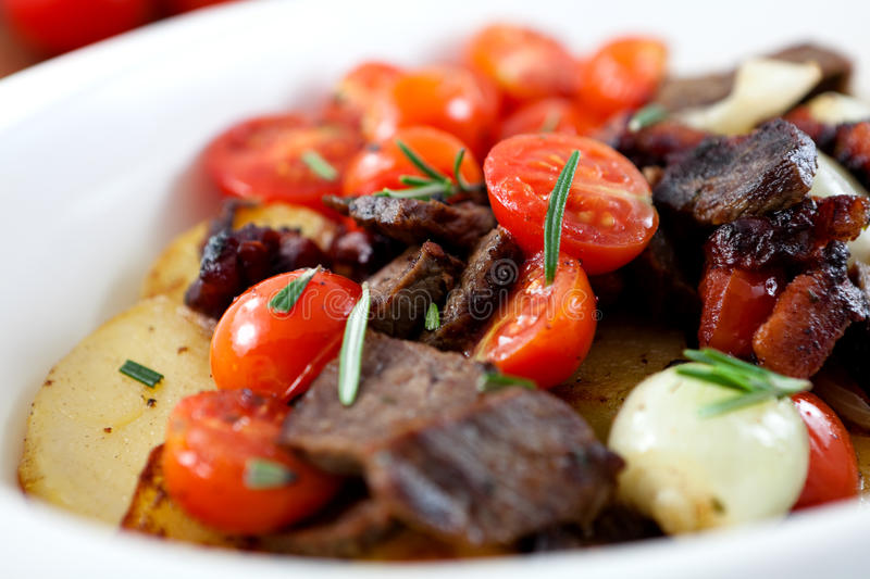 Braised beef with onions,cherry tomatoes and potat. Closeup of braised beef with cherry tomatoes,onions,potatoes and rosemary royalty free stock photo