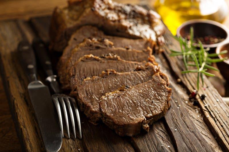 Braised brisket on cutting board. Braised beef brisket with herbs and spices on cutting board royalty free stock image