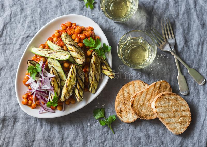 Braised chickpeas in tomato sauce, grilled eggplant and zucchini, white wine, grilled bread - a delicious appetizer or snack. Vege royalty free stock images