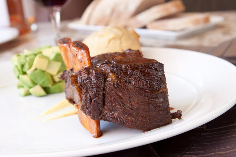 Braised Cumbrae's Short Rib. Short rib, cooked to perfection, served with savoury pound cake, avocado cubes, turnip puree and county cider reduction royalty free stock photos