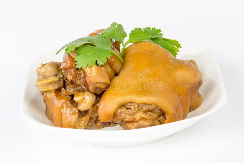 Braised pig knuckles. On a white plate stock photos