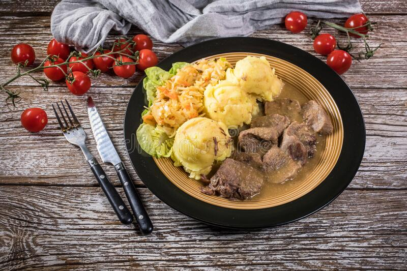 Braised pork tongues in horseradish sauce. Served with potatoes and salad stock photos