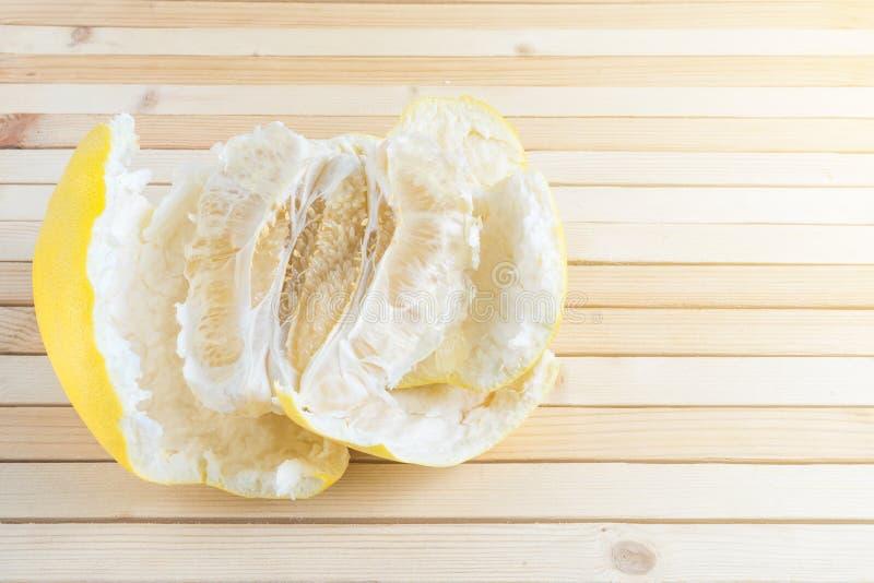Braja dojrzały egzotyczny owocowy pomelo z łupą na drewnianym tle w słońcu zdjęcie stock