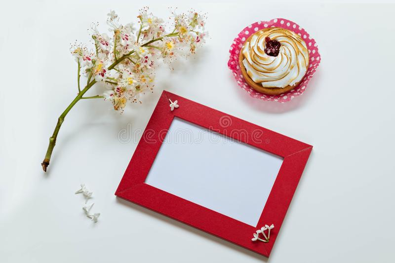 Branch of the blossoming chestnut, red frame for a congratulation inscription, lemon cake on a white background. stock image