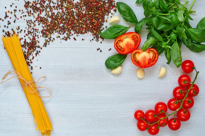Branch of cherry tomatoes, basil, garlic, various pepper and uncooked pasta on the gray background. Top view with copy space stock photos