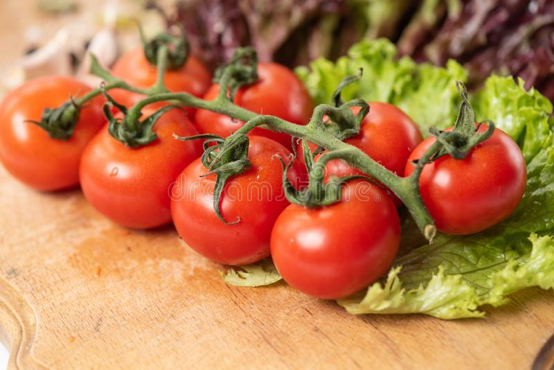 Branch of cherry tomatoes on wooden table closeup royalty free stock photography