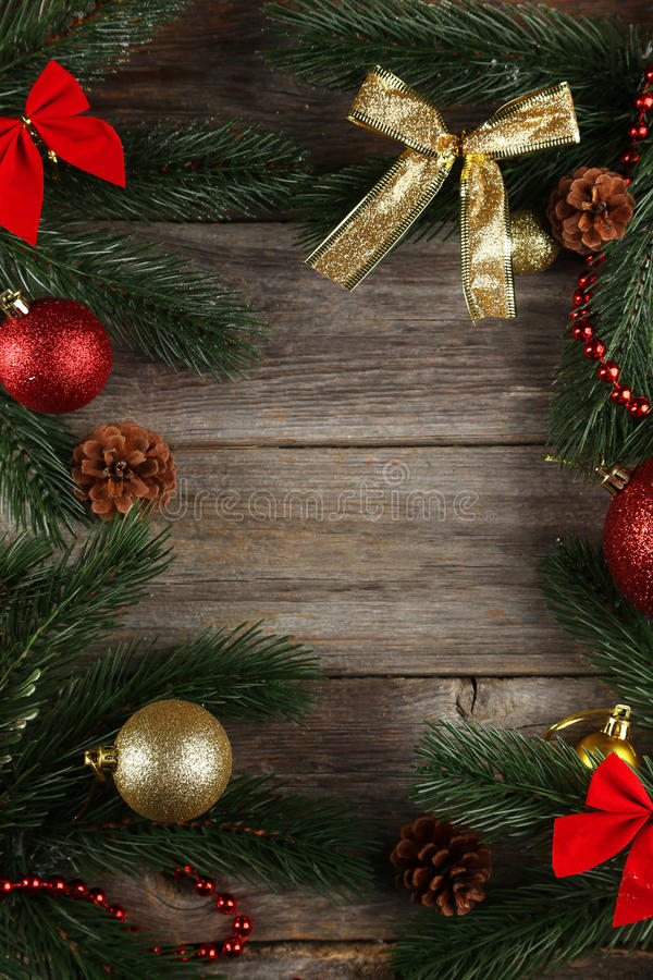 Branch of Christmas tree with balls on grey wooden background royalty free stock photo
