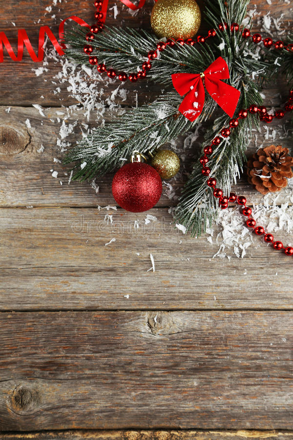 Branch of Christmas tree with balls on wooden background royalty free stock image