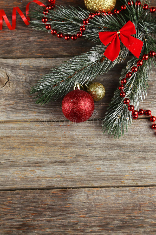 Branch of Christmas tree with balls on wooden background stock photo