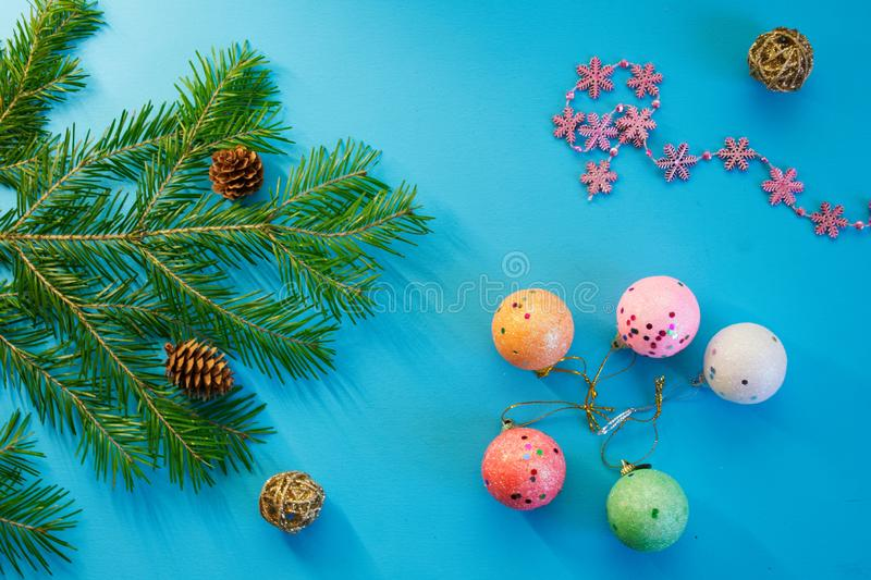 Branch of a Christmas tree, cones, toys, snowflakes and multicolored balls on a blue background. Waiting for the holiday stock photo