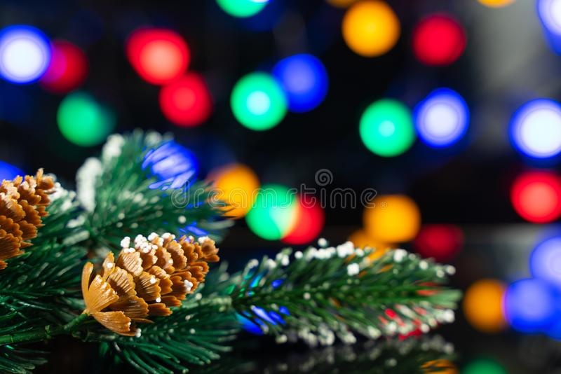 Branch of the Christmas tree with a lump on the black table. A branch of the Christmas tree with a lump on a black table with a beautiful reflection and colored stock image