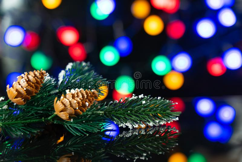 Branch of the Christmas tree with a lump on the black table. A branch of the Christmas tree with a lump on a black table with a beautiful reflection and colored stock photos