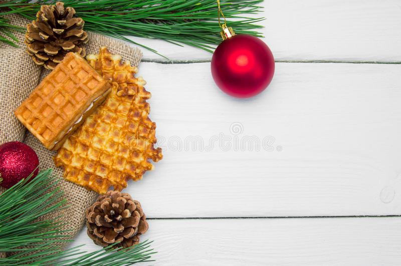 Branch christmas tree with red ball and waffles on burlap on white wooden vintage background. Branch christmas tree with red ball and waffles on burlap on white royalty free stock image