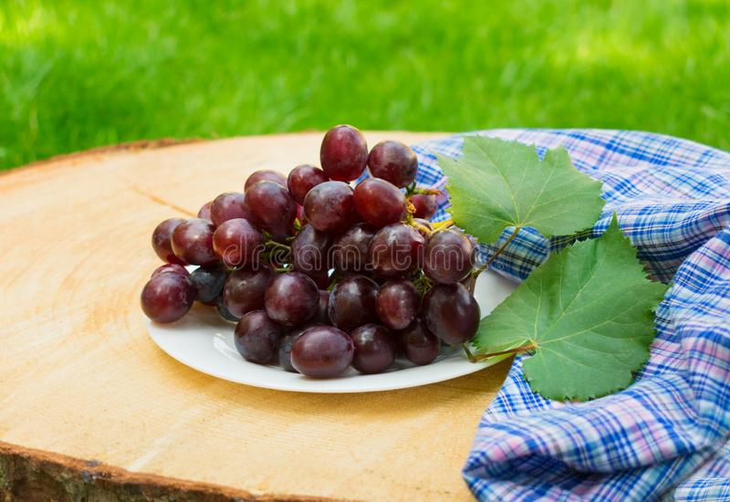 Branch of grapes with leaves on a plate on a wooden table against the background of green grass. Close-up. stock photos