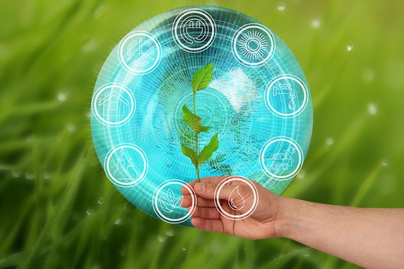 Branch in hand on a beautiful autumn background model of the planet Earth and environmental protection elements icons,. Environmental concept, close-up stock photography