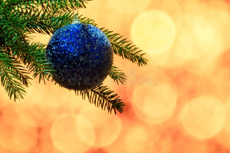 Branch of spruce with blue Christmas toy. Blue Christmas toy hanging on a branch of spruce with yellow bokeh on the background stock image