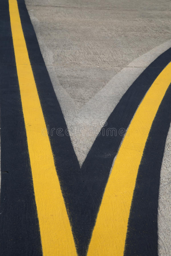 Branch yellow lines painting on airport runway.  stock photos
