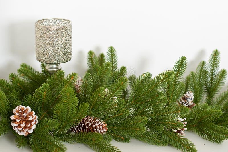 Branche d'arbre de Noël avec des cônes de pin et un bougeoir sur un fond blanc photos stock