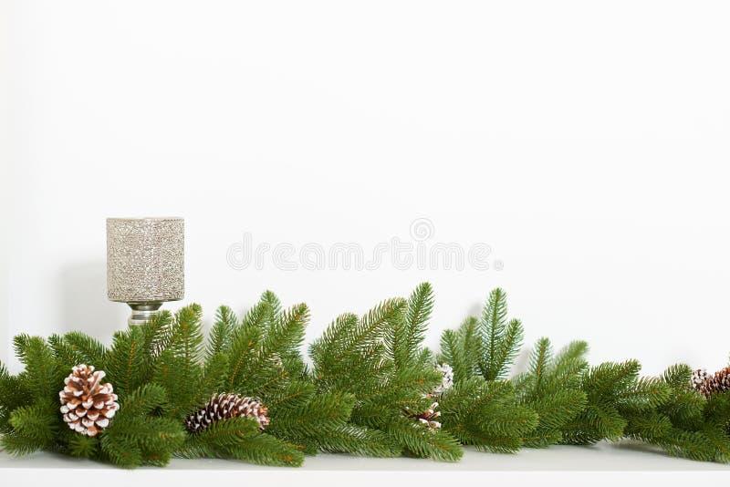Branche d'arbre de Noël avec des cônes de pin et un bougeoir sur un fond blanc photo libre de droits