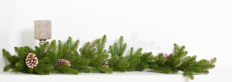 Branche d'arbre de Noël avec des cônes de pin et un bougeoir sur un fond blanc photographie stock libre de droits