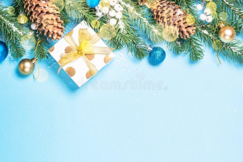 Branche d'arbre de sapin de neige avec les décorations bleues et d'or et boîte actuelle sur le fond bleu photo libre de droits