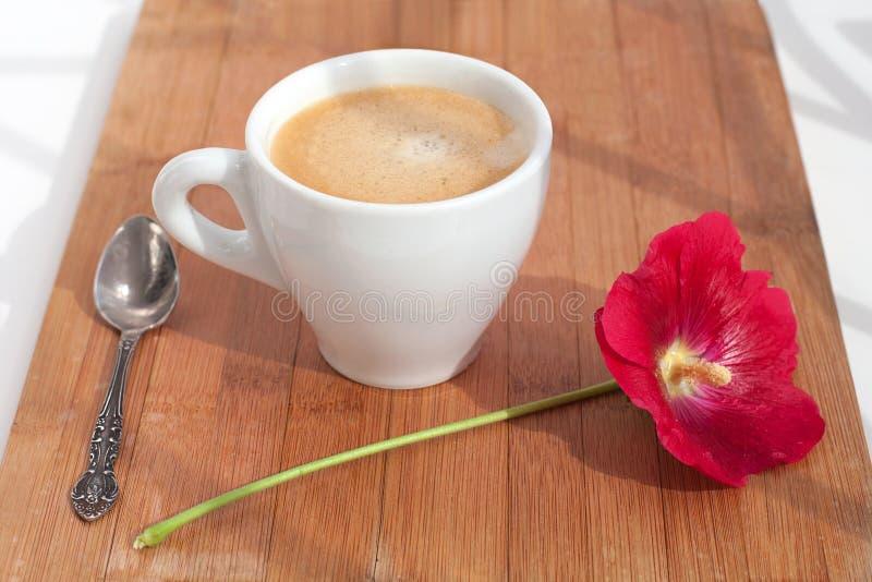 Branche de fleur rouge de mauve et de tasse blanche de café chaud avec la mousse avec la cuillère d'argent sur la table sur le pl images libres de droits