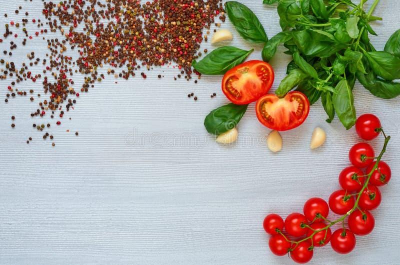 Branche des tomates-cerises, du basilic, de l'ail et du divers poivre sur le fond gris Vue supérieure avec l'espace de copie photo libre de droits