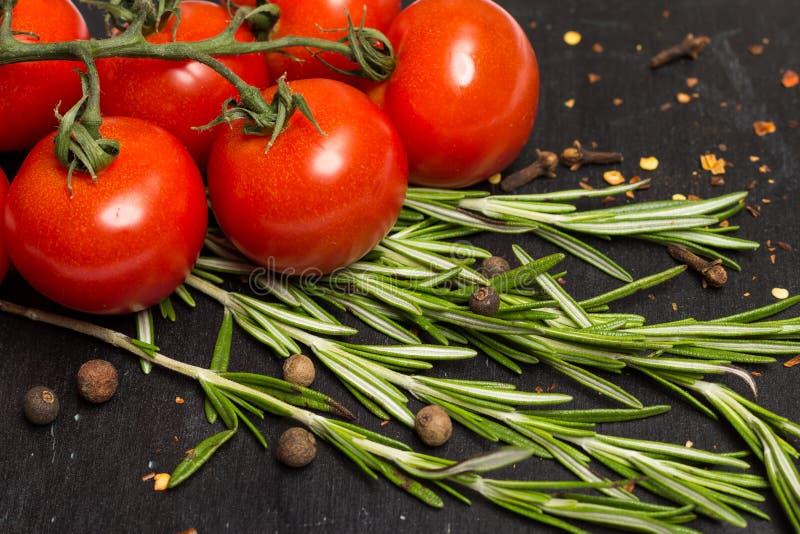 Branche des tomates mûres de cerise, romarin frais, poivre de Jamaïque, photographie de nourriture photos libres de droits