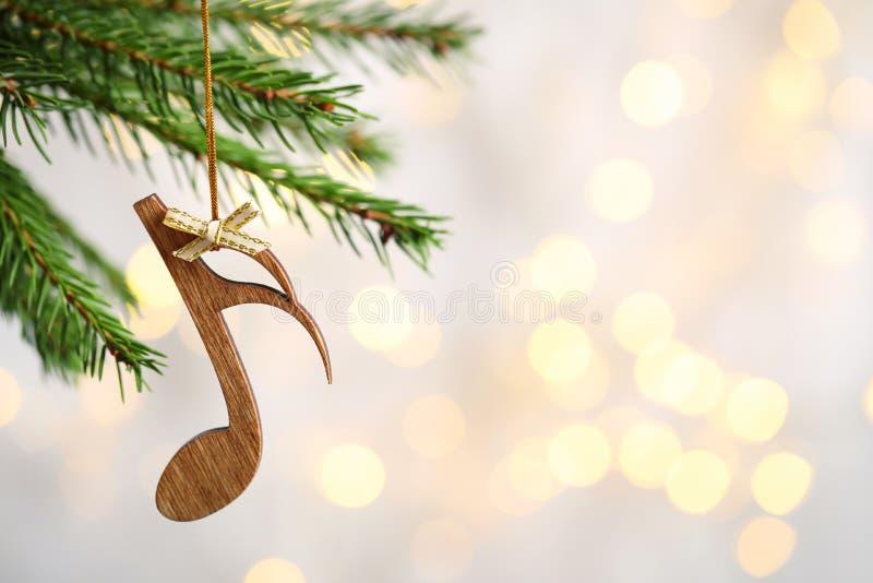 Branche du sapin avec note en bois contre feux flous. Musique de Noël photos stock