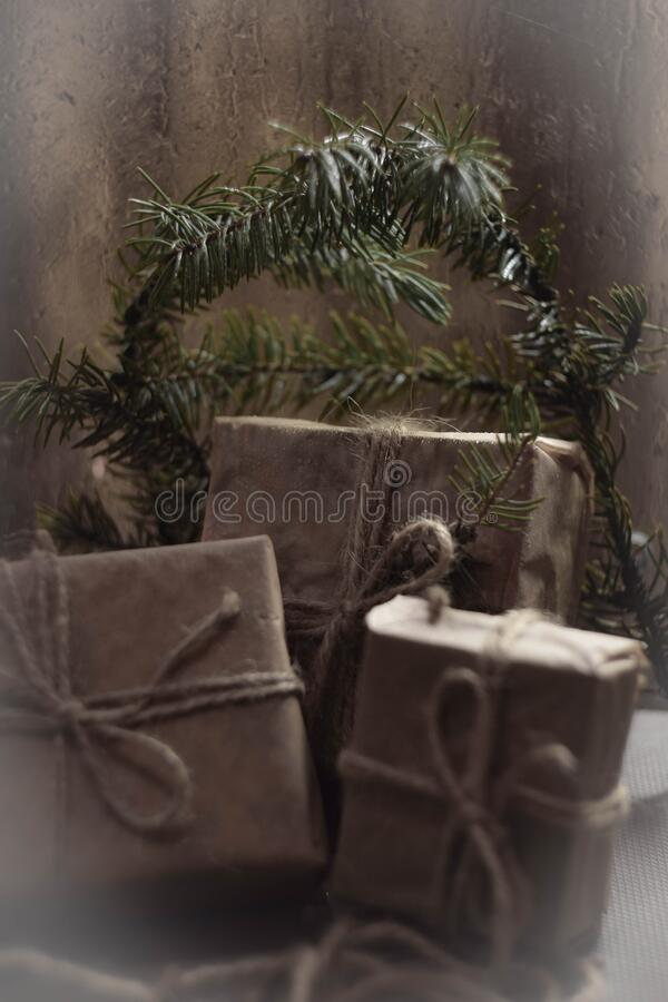 Branches ate and wet glass with, gifts for the holiday, vintage. Gifts vintage of coarse paper and coarse thread,Holiday in winter or summer but with branches stock photography