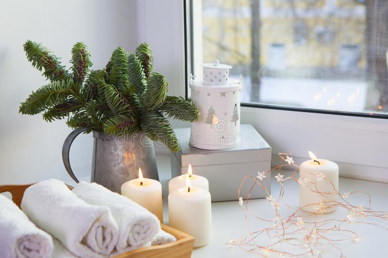 Branches of Christmas tree in a zinc pitcher on the window. The garland is lit and the candles are burning. stock photography