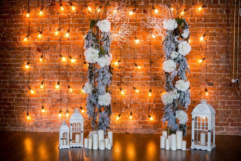 Branches coniféres avec des buissons d'hortensia, des bougies et des ampoules sur un fond de brique images libres de droits