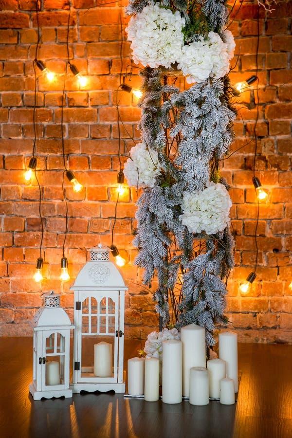 Branches coniféres avec des buissons d'hortensia, des bougies et des ampoules sur un fond de brique, cadre vertical images libres de droits