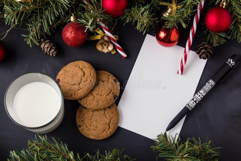 Branches d'arbre de Noël décorées de balles sur une table noire à côté de la liste des cadeaux images libres de droits