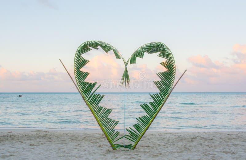Branches de paume attachées dans la forme d'un coeur sur la plage photographie stock