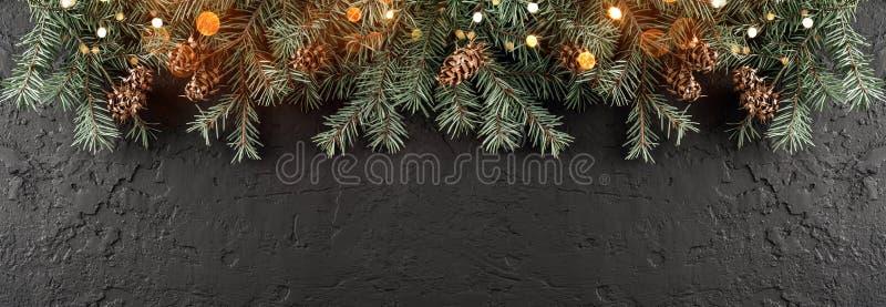 Branches de sapin de Noël avec des lumières sur le fond noir foncé Carte de Noël et de bonne année, bokeh, étincellement, rougeoy images stock