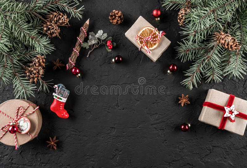 Branches de sapin de Noël, cônes de pin, cadeaux sur le fond foncé Thème de Noël et de nouvelle année , neige Configuration plate image libre de droits