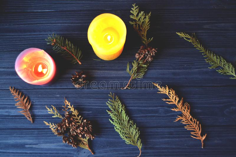 The branches of fir-tree on the dark blue wooden background. Natural pattern with candles. Atmospheric photo. stock photos