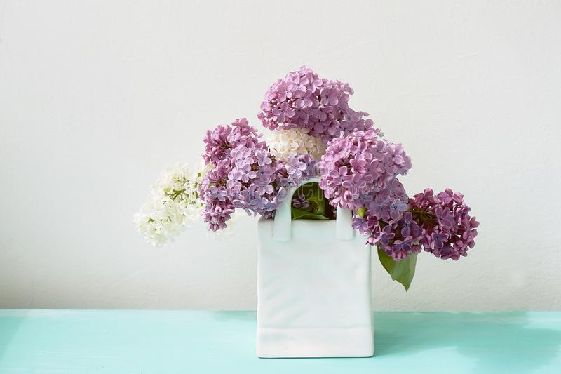 Branches of white and purple lilac.Natural wealth. In a white vase package. stock photo